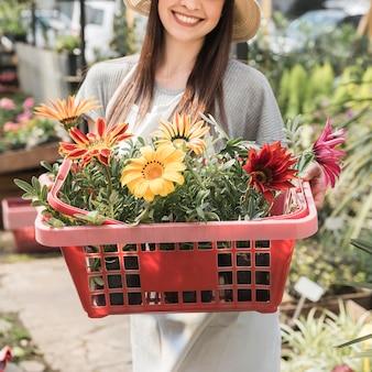 Primer plano de una mujer feliz celebración de contenedor con flores de colores
