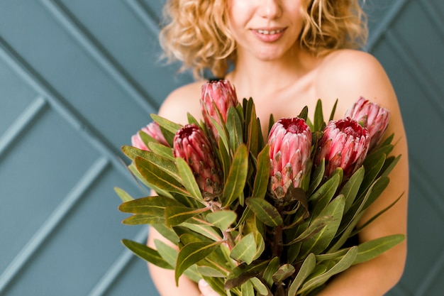 Primer plano mujer feliz con ramo de flores en el interior