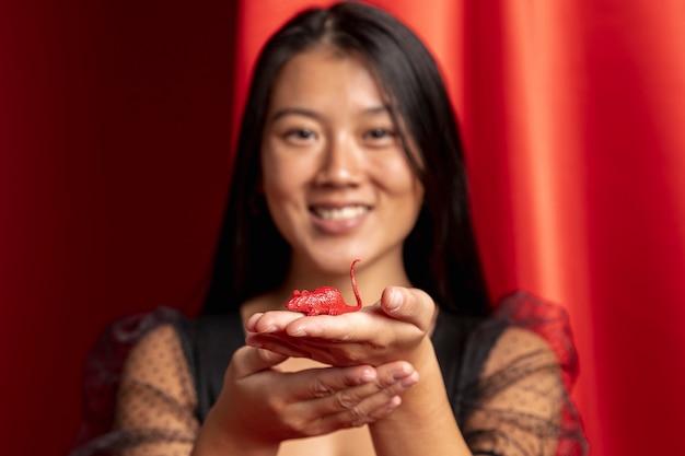 Primer plano de mujer con figurilla de rata para año nuevo chino