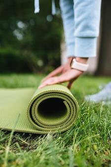 Primer plano de mujer fitness rollo plegable después de hacer ejercicio en el parque
