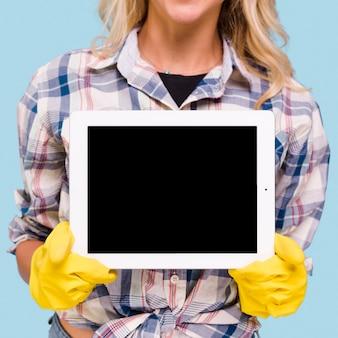 Primer plano de mujer con guantes amarillos con tableta digital de pantalla en blanco