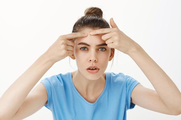 Primer plano de mujer haciendo estallar el grano, eliminando el acné de la frente