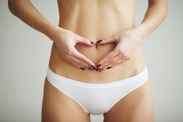 Primer plano de mujer haciendo forma de corazón con las manos sobre el estómago