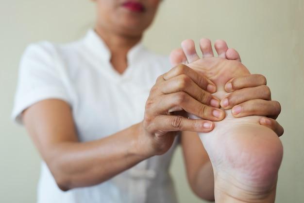 Primer plano de mujer haciendo masaje de pies en el spa.