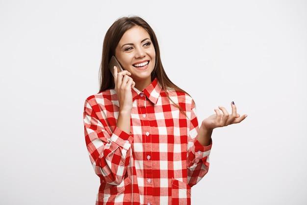 Primer plano de mujer hermosa en camisa de moda hablando por teléfono