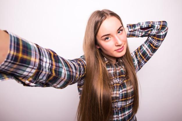 Primer plano de mujer hermosa joven tomando selfie. pared blanca aislada
