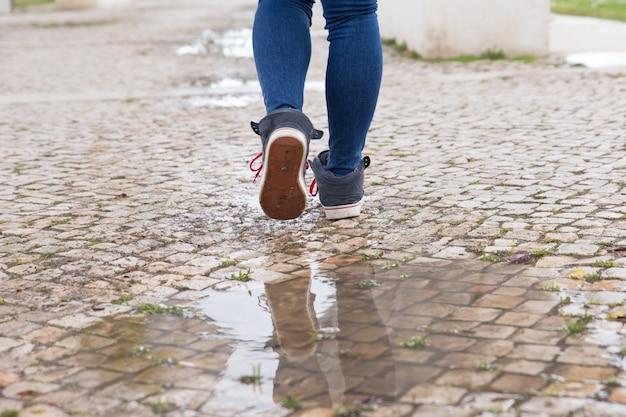 Primer plano de mujer irreconocible caminando en el camino de piedra