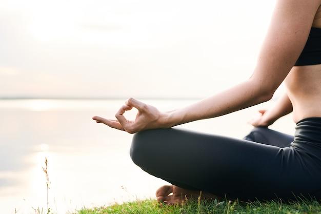 Primer plano de mujer irreconocible en leggings sentada en la orilla del lago y practicando yoga en unidad con la naturaleza