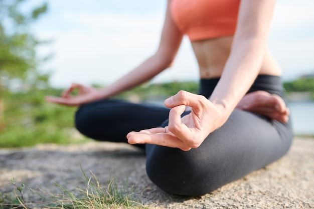Primer plano de mujer irreconocible en leggings sentada en posición de loto y manteniendo las manos en mudra durante la meditación al aire libre