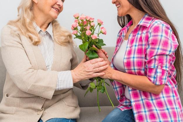 Primer plano de mujer joven adulta alegre y senior sosteniendo rosas