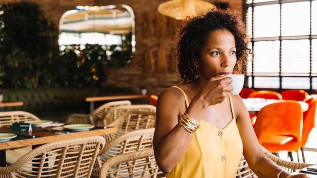 Primer plano de una mujer joven afroamericana tomando café