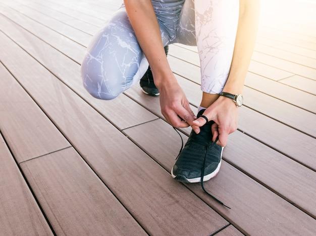 Primer plano, de, mujer joven, atar, zapato deportivo