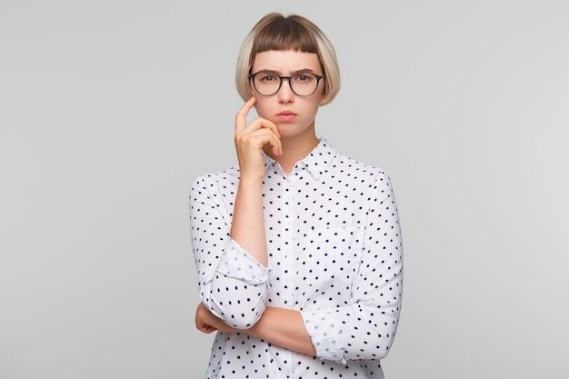 Primer plano de una mujer joven bastante rubia pensativa viste camisa de lunares