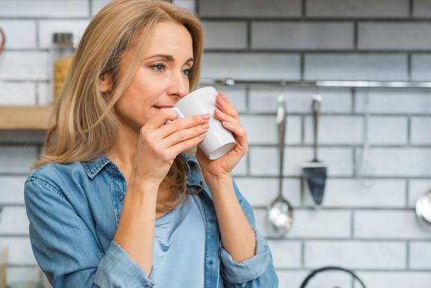 Primer plano, de, un, mujer joven, bebida, taza de café
