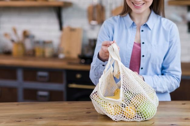 Primer plano mujer joven con bolsa con frutas frescas