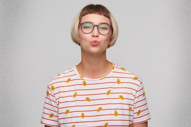 Primer plano de una mujer joven y bonita sonriente viste camiseta a rayas