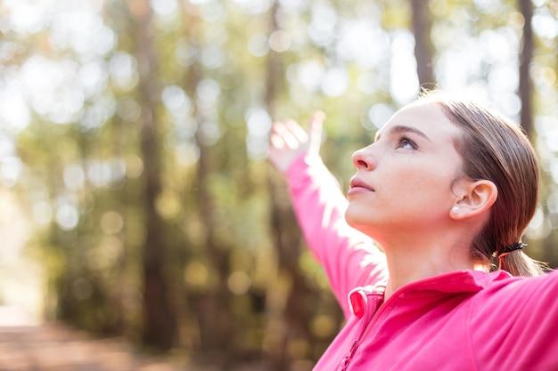 Primer plano de mujer joven con los brazos abiertos al aire libre