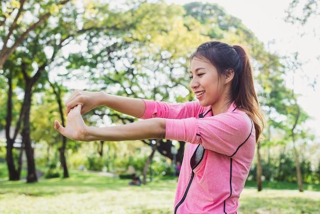 Primer plano de una mujer joven calienta su cuerpo estirando los brazos
