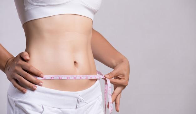 Primer plano de una mujer joven y delgada que mide su cintura delgada con una cinta métrica