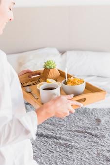 Primer plano de mujer joven con desayuno por la mañana en la bandeja de madera