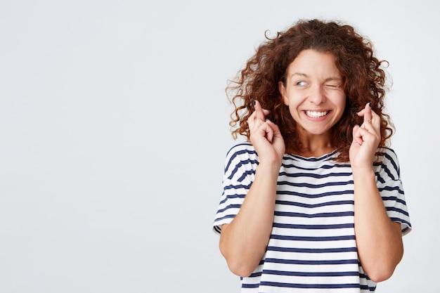 Primer plano de una mujer joven encantadora feliz con el pelo rizado viste camiseta a rayas