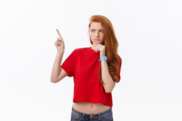 Primer plano de mujer joven estricta estricta viste camisa roja se ve estresado y apuntando hacia arriba con el dedo aislado sobre fondo blanco