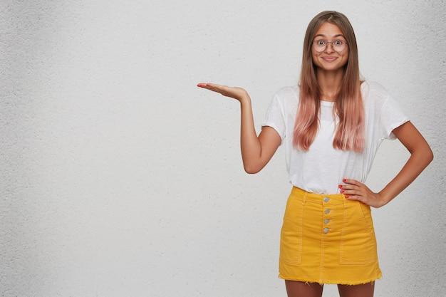 Primer plano de una mujer joven feliz asombrada que viste camiseta, falda amarilla y gafas se ve sorprendido y tiene copyspace en la palma aislada sobre la pared blanca