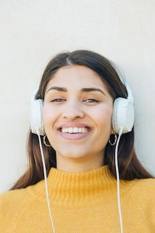 Primer plano de una mujer joven feliz usando auriculares