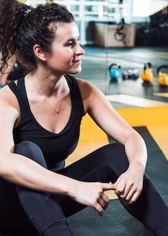 Primer plano de una mujer joven en forma sentada en el piso en el gimnasio