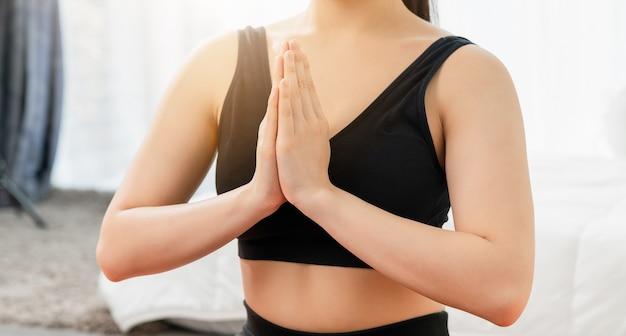 Primer plano de una mujer joven haciendo ejercicios de yoga en la sala de estar en casa