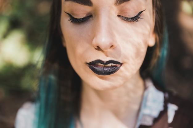 Primer plano de mujer joven con lápiz labial negro en sus labios