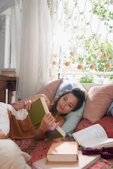 Primer plano de una mujer joven leyendo un libro en la cama