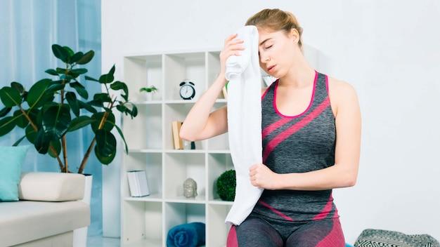 Primer plano de mujer joven limpiando el sudor con una toalla blanca en la sala de estar