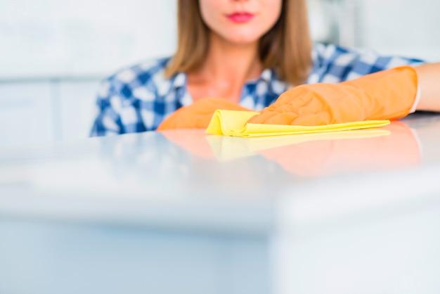 Primer plano de mujer joven limpiando la superficie blanca con plumero amarillo