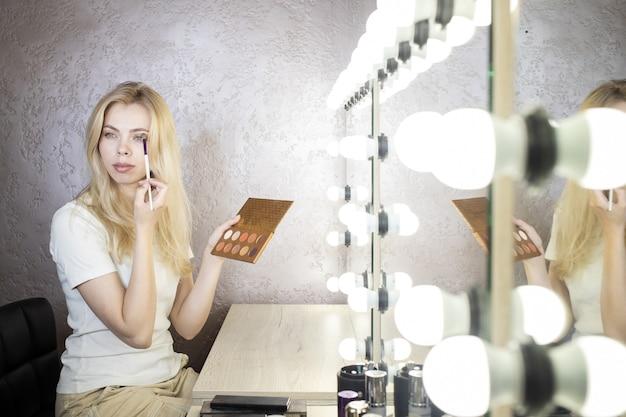 Primer plano, de, un, mujer joven, llevando, maquillaje, en, un, belleza, estudio