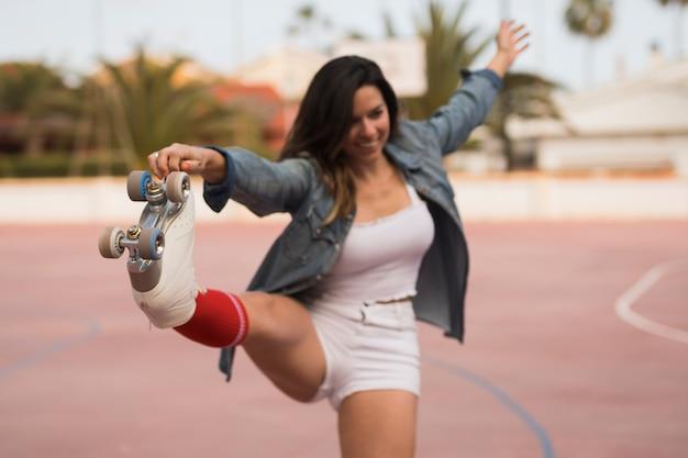 Primer plano, de, mujer joven, llevando, patín de ruedas, estirar, el suyo, pierna