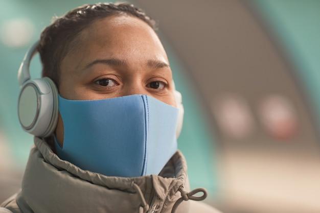 Primer plano de una mujer joven con máscara protectora mirando a la cámara mientras escucha música en auriculares
