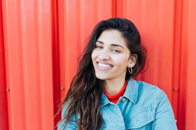 Primer plano de mujer joven mirando a la cámara sentado contra el telón de fondo metálico rojo