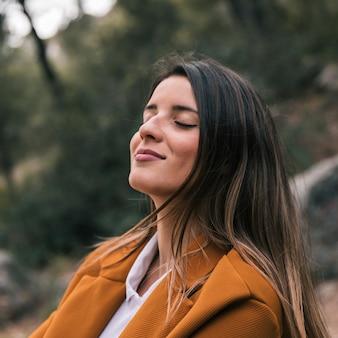 Primer plano de una mujer joven con el ojo cerrado disfrutando de la naturaleza