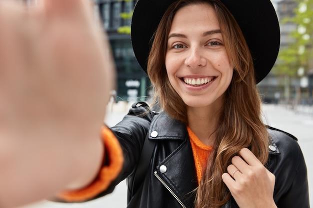 Primer plano de una mujer joven optimista tiene la mano extendida