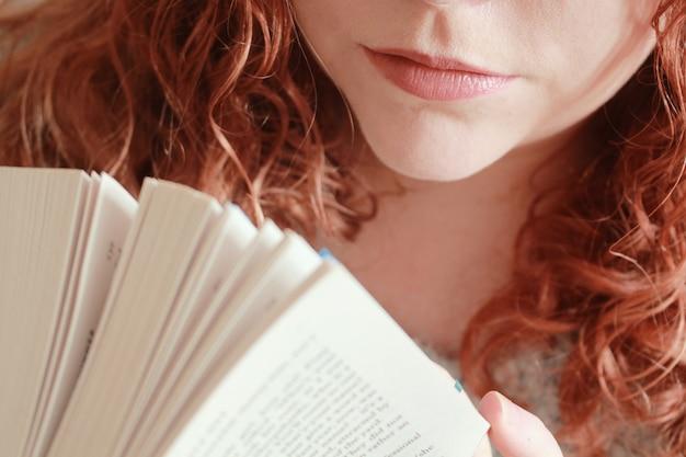 Primer plano de una mujer joven con pelo rojo sosteniendo un libro bajo las luces