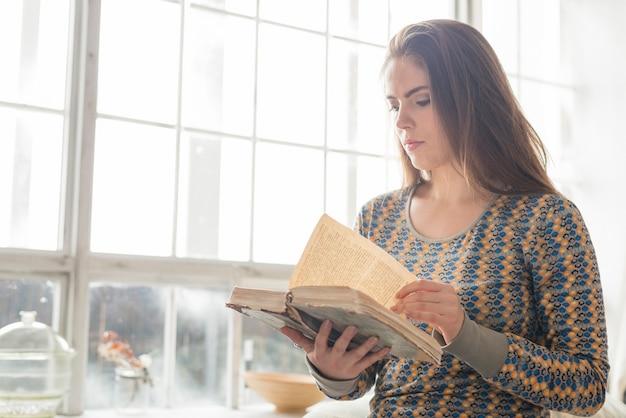 Primer plano de una mujer joven de pie cerca de la ventana de libro de lectura
