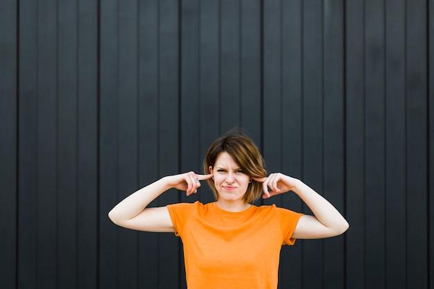 Primer plano de una mujer joven de pie contra la pared negra cerrando las orejas con dos dedos