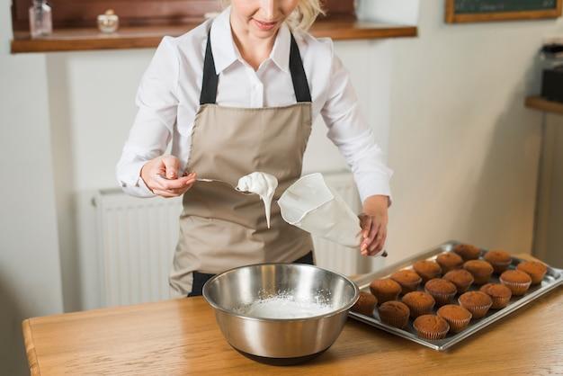 Primer plano de mujer joven poner crema blanca en la bolsa de pastelería