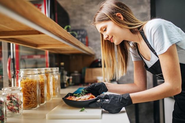 Primer plano de mujer joven preparando pasta con tomate sous para la cena.