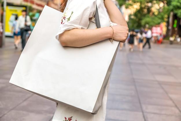 Primer plano, de, mujer joven, proceso de llevar, bolsas de compras, mientras, ambulante, por, el, calle