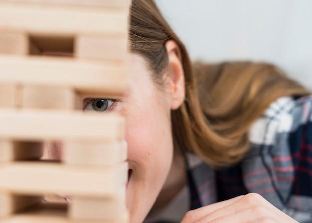 Primer plano de mujer joven que mira a escondidas desde el bloque de madera de la torre