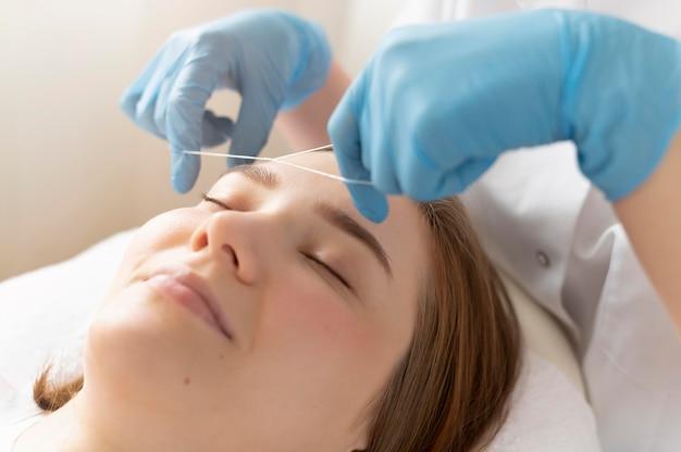 Primer plano de mujer joven recibiendo un tratamiento de cejas