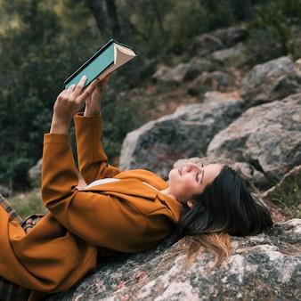 Primer plano, de, un, mujer joven, reclinado, roca, leer el libro