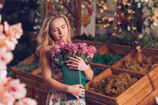 Primer plano de mujer joven rubia abrazando la maceta de rosas rosadas